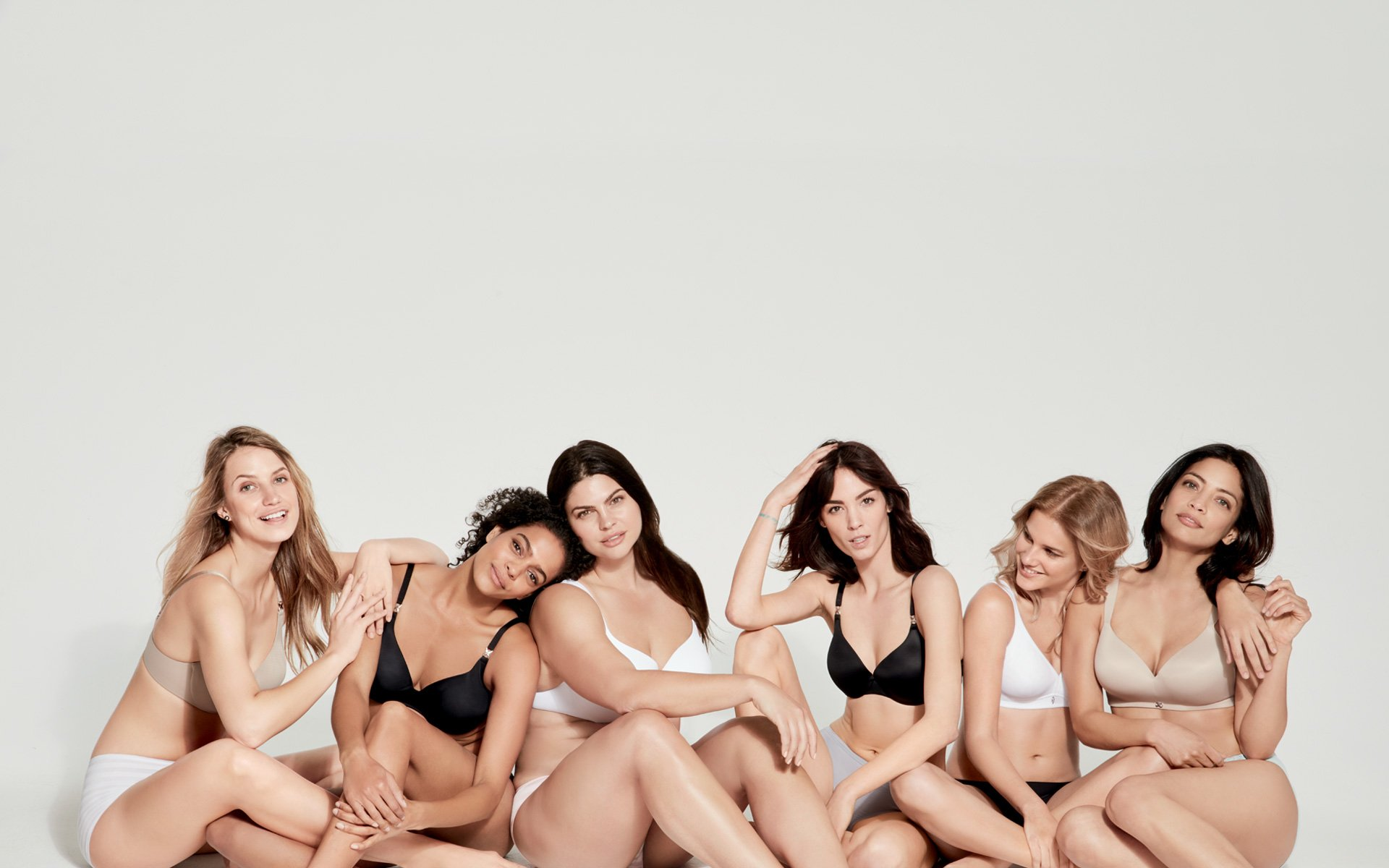 Women lined up lounging in different availible styles and colors of the RealFit Bra