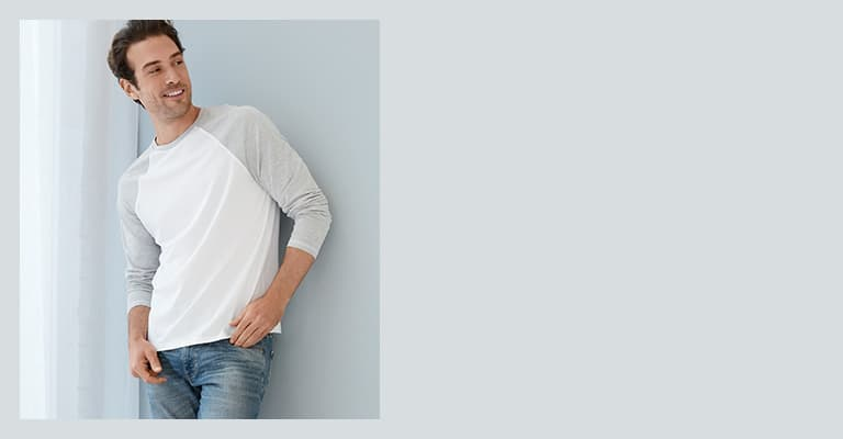Young man leaning against a wall wearing a baseball tee and jeans